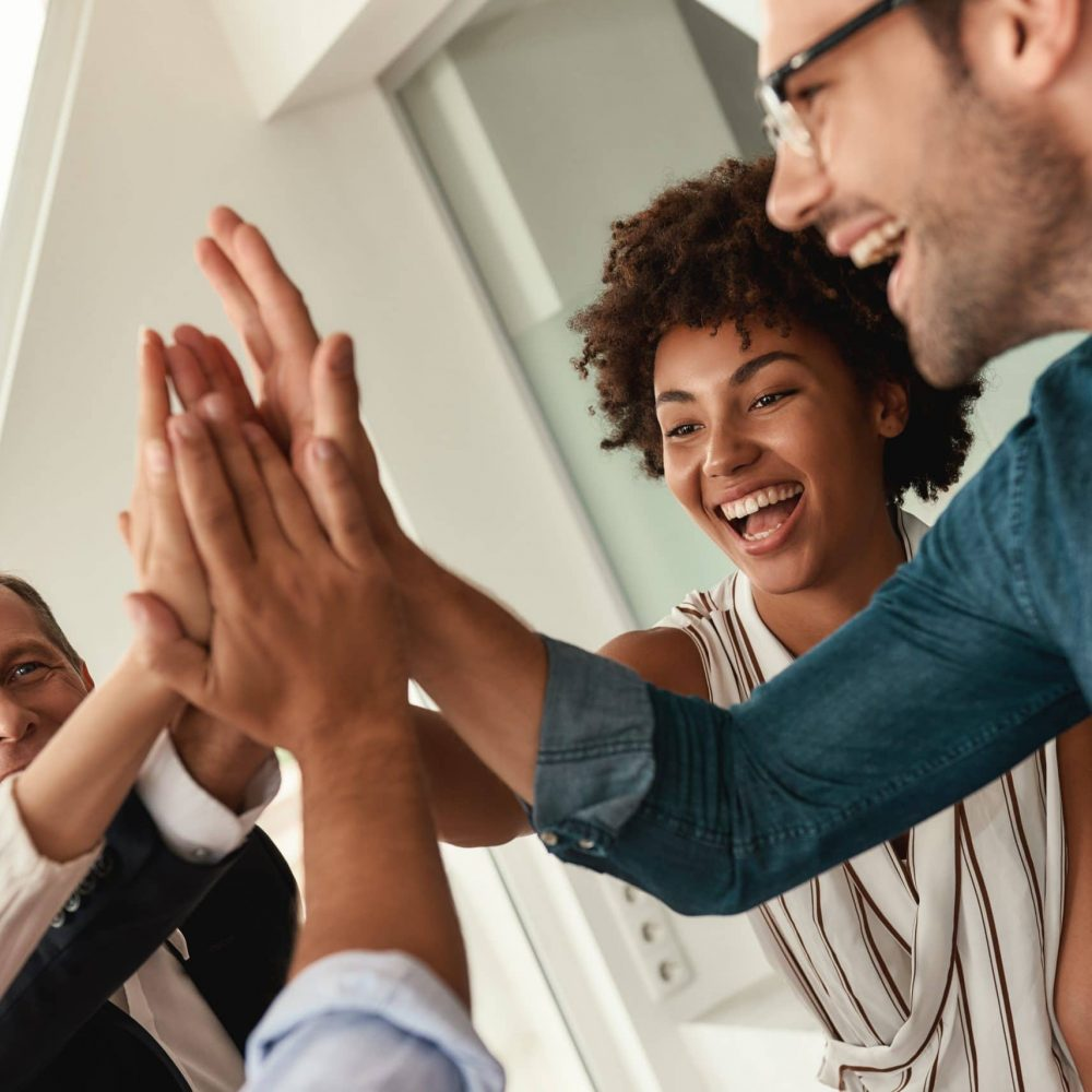 Celebrating success. Business people giving each other high-five and smiling while working together in the modern office. Teamwork